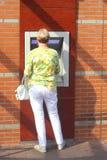 A mulher obtém o dinheiro de uma máquina de dinheiro, Holanda Fotografia de Stock