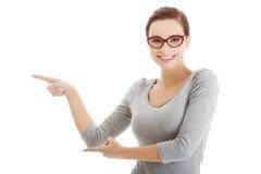 Mulher ocasional bonita nos monóculos que aponta de lado. imagem de stock