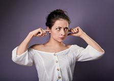 A mulher ocasional infeliz for?ada fechou as orelhas os dedos porque n?o queira ouvem todos os sons e ru?do no fundo roxo closeup imagem de stock