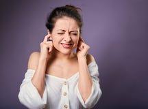 A mulher ocasional infeliz forçada fechou as orelhas os dedos porque não queira ouvem todos os sons e ruído fotografia de stock