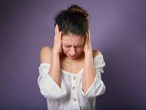 A mulher ocasional infeliz forçada fechou as orelhas os dedos porque não queira ouvem todos os sons e ruído no fundo roxo closeup imagens de stock