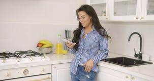 Mulher ocasional nova com o smartphone na cozinha video estoque