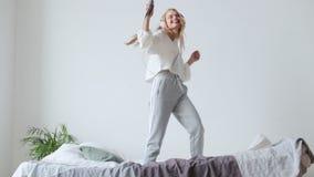 Mulher ocasional nova nos fones de ouvido que escuta a música e que salta na cama dentro video estoque