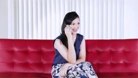 Mulher ocasional que fala com o telefone celular no sofá filme