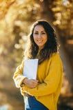 Mulher ocasional que guarda um livro no outono no parque foto de stock royalty free