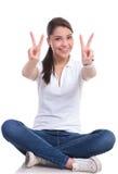 A mulher ocasional senta-se & vitória Fotos de Stock Royalty Free