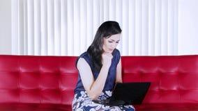 Mulher ocupada com o portátil no sofá vermelho vídeos de arquivo
