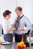 Mulher ocupada que amarra o laço do marido foto de stock