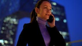 Mulher ocupada que fala no telefone celular contra o arranha-céus moderno na baixa da cidade video estoque