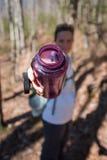 A mulher oferece a garrafa de água roxa Foto de Stock Royalty Free