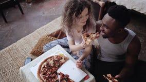 A mulher oferece a pizza equipar, mas comer só a fatia Pares multirraciais que têm o divertimento durante a refeição com fast foo fotografia de stock royalty free