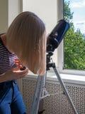 A mulher olha através de uma janela em um telescópio foto de stock royalty free