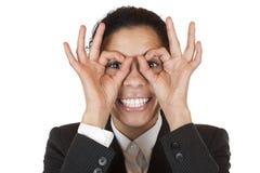 A mulher olha através dos binóculos do dedo Fotos de Stock Royalty Free