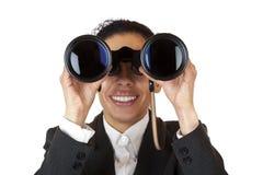 A mulher olha através dos binóculos e encontrou o negócio Foto de Stock Royalty Free