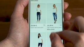 A mulher olha calças de brim na loja em linha no smartphone filme