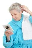 A mulher olha em um espelho Imagem de Stock Royalty Free