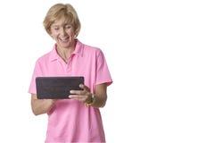A mulher olha entusiasmado em um tablet pc Fotografia de Stock Royalty Free