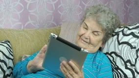 A mulher olha imagens usando uma tabuleta digital video estoque