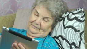 A mulher olha imagens usando uma tabuleta digital vídeos de arquivo