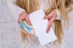 a mulher olha no envelope imagem de stock