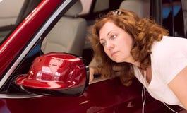 A mulher olha no espelho imagens de stock