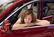 A mulher olha no espelho de carro imagem de stock
