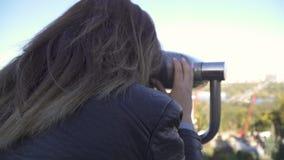 A mulher olha no visor binocular na arquitetura da cidade filme