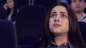 A mulher olha o drama no cinema fotos de stock
