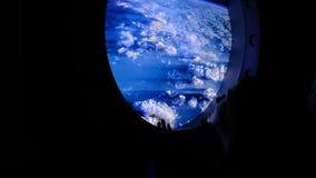 A mulher olha para fora na vigia no espaço foto de stock