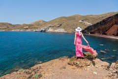 A mulher olha a praia vermelha em Santorini, Grécia Imagens de Stock