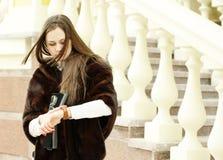 A mulher olha seu relógio perto Fotografia de Stock Royalty Free