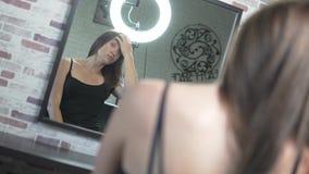A mulher olha si mesma no espelho no salão de beleza vídeos de arquivo
