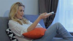 A mulher olha a tevê em casa vídeos de arquivo