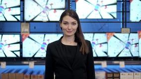 A mulher olha tevês do LCD no supermercado, loja video audio com consultante bonito filme