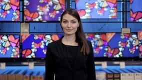 A mulher olha tevês do LCD no supermercado, loja video audio com consultante bonito Imagens de Stock Royalty Free