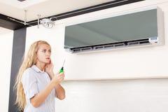 A mulher olha um condicionador de ar quebrado foto de stock