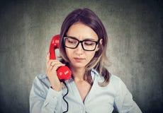 Mulher olhando de sobrancelhas franzidas que tem o problema ao falar no telefone vermelho no fundo cinzento fotografia de stock royalty free