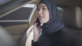 Mulher oriental de sorriso nova na roupa muçulmana moderna e na mantilha bonita que fala pelo telefone celular que senta-se dentr filme
