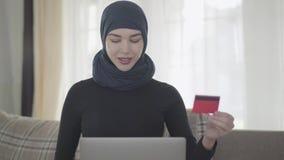 Mulher oriental de sorriso nova na roupa muçulmana moderna e na mantilha bonita usando um cartão de crédito para pagar a utilizaç vídeos de arquivo