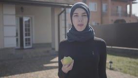 Mulher oriental de sorriso nova na roupa muçulmana moderna e posição preta bonita da mantilha na frente de uma casa grande filme