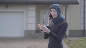 Mulher oriental de sorriso nova na roupa traseira e na mantilha bonita que fala pelo telefone celular que guarda as chaves à disp video estoque