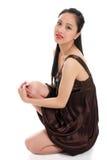Mulher oriental nova em um vestido marrom que senta-se para baixo Fotografia de Stock Royalty Free