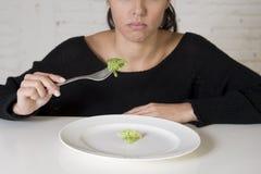Mulher ou adolescente com a forquilha que come o prato com alface pequena ridícula como seu símbolo do alimento da dieta louca fotografia de stock