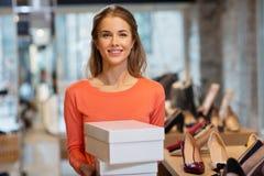 Mulher ou assistente de loja com as caixas de sapata na loja fotografia de stock royalty free