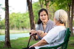 Mulher ou mãe com sintomas depressivos ou paciente idoso de alzheimer, cuidador fêmea asiático ou filha guardando o paciente idos fotos de stock