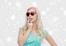 A mulher ou o adolescente feliz no coração deram forma a óculos de sol fotos de stock