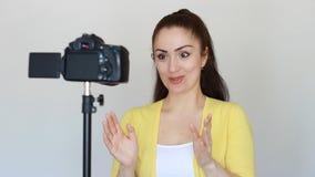 A mulher ou o blogger de sorriso feliz gesticulam com mãos e falam, gravando o vídeo em uma câmera que seja fixada a um tripé den vídeos de arquivo