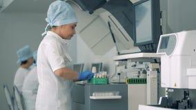 A mulher põe amostras de sangue novas de uma cremalheira na máquina médica especial em uma clínica HD vídeos de arquivo