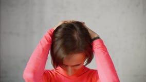 A mulher põe as mãos sobre a parte traseira de cabeça e as inclinações dirigem para a frente o esticão dos músculos do pescoço filme