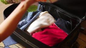 A mulher põe coisas em uma mala de viagem vídeos de arquivo